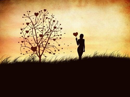 Femme-avec-un-coeur-dans-la-main-devant-l-arbre-des-sentiments