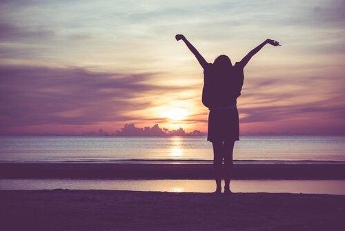 Femme-etirant-ses-bras-devant-coucher-de-soleil
