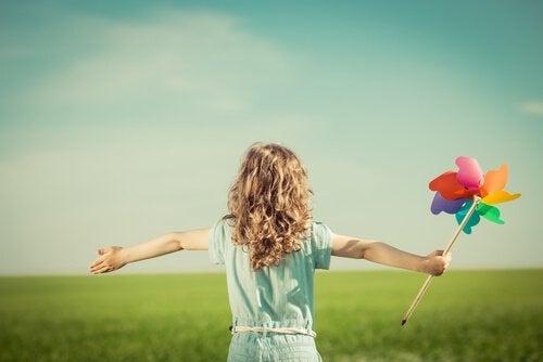 Jeune-fille-heureuse-jouant-dans-un-champ