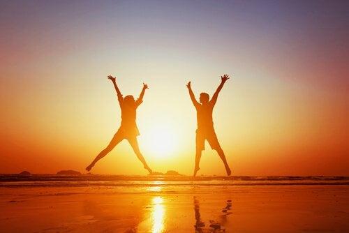couple-heureux-sautant-sur-la-plage
