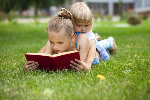 Petite-fille-lisant-un-livre-sur-l'herbe-avec-sa-soeur