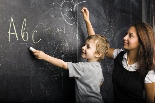 Maestra-con-niño-en-la-pizarra-dibujando