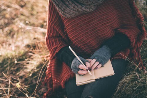 Mains-de-femme-ecrivant-sur-un-carnet-dans-un-champ