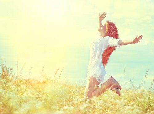 Mujer-feliz-saltando-en-el-campo