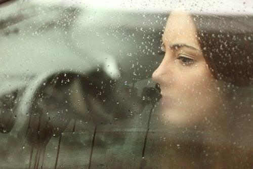 Mujer-triste-llorando-tras-un-cristal-con-gotas-de-lluvia