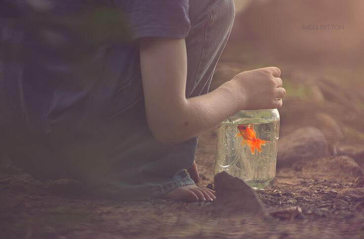 enfant avec un bocal contenant un poisson rouge