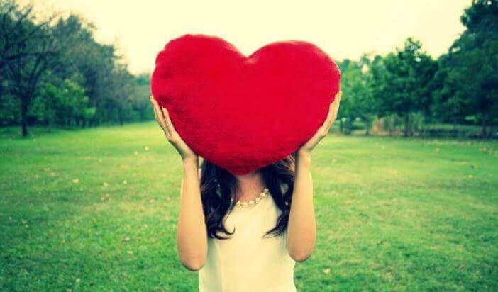 femme avec un coussin en forme de coeur