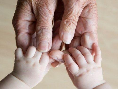 mains d'une personne agee avec celles d'un bebe