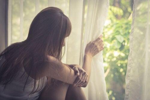 Mujer-triste-pensando-en-su-vida-mirando-por-la-ventana-1