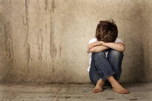 Enfant-triste-assis-sur-le-sol-les-bras-croises