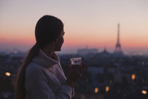 Femme-profitant-de-la-vue-de-paris-avec-un-cafe