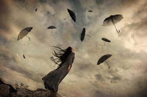 Femme-regardant-des-parapluies-voler-dans-le-ciel
