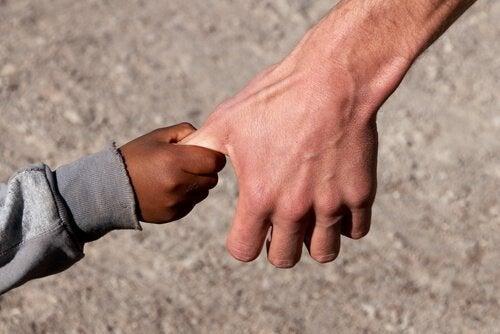 Mano-de-un-niño-sirio-cogiendo-la-de-un-adulto-de-raza-blanca