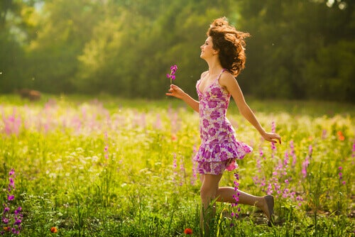 Mujer-caminando-entre-flores-sonriendo-y-feliz