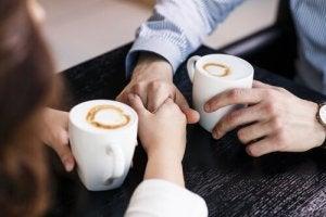 Couple-parlant-se-prenant-les-mains-cafe