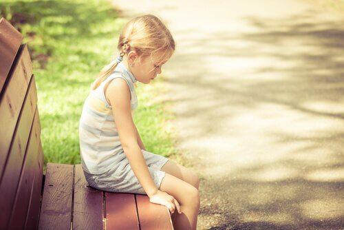 Enfant-blonde-assise-sur-un-banc-triste