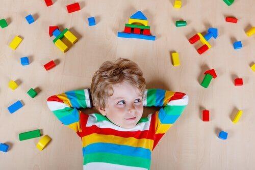 Enfant-sur-le-sol-entoure-de-jouets