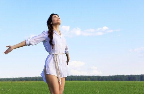 Mujer-con-los-brazos-abiertos-vestida-de-blanco-en-el-campo