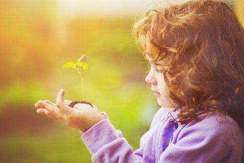 fille-regardant-une-plante-pousser