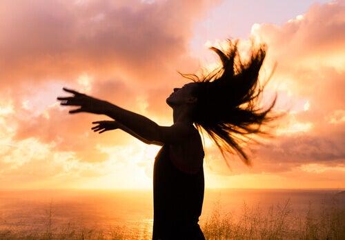 femme-avec-les-bras-ouverts-coucher-de-soleil