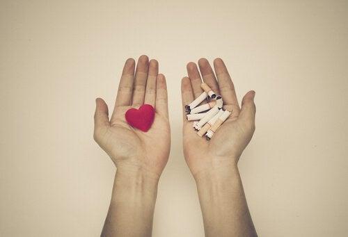 mano-con-un-corazon-rojo-y-mano-con-cigarros