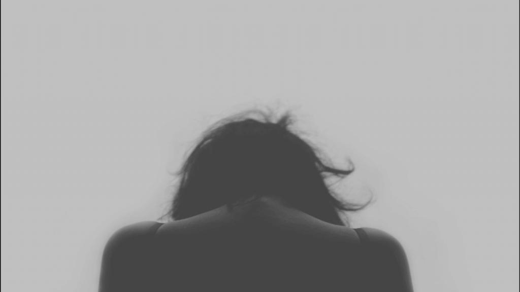 femme de dos avec la tete baissée