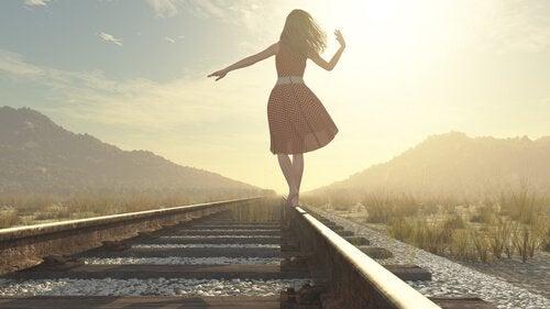 femme heureuse sur une voie ferrée