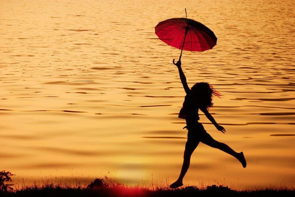 femme pleine de motivation sautant avec un parapluie