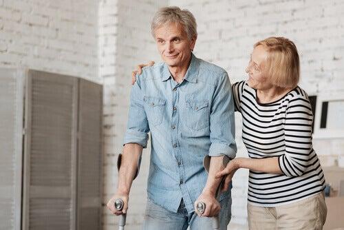 homme marchant avec des béquilles aidé par une femme
