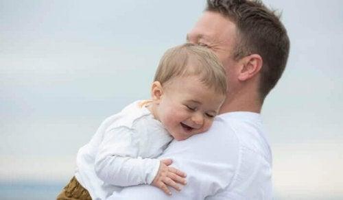enfant riant dans les bras de son père