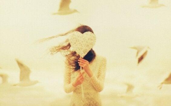 femme se cachant derrière un coeur