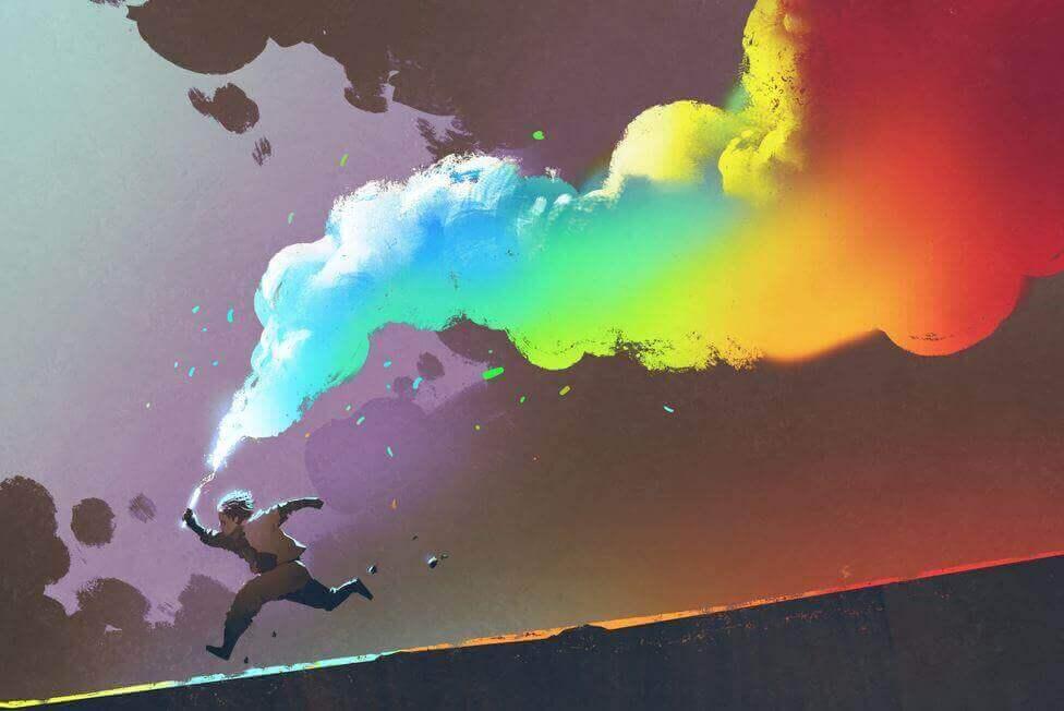 enfant avec un fumigène dégageant de la fumée arc en ciel