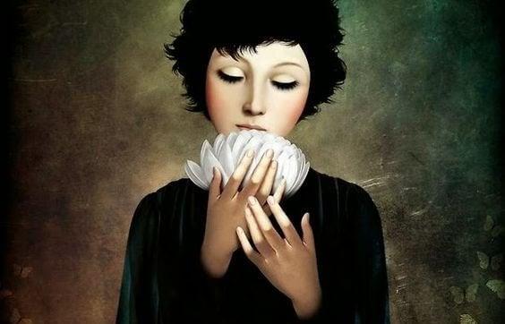 femme avec une fleur blanche dans les mains