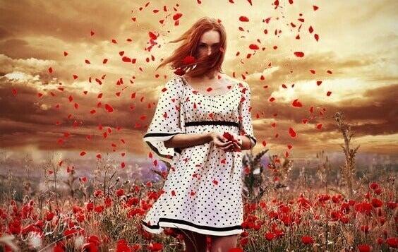 femme dans un champ de fleurs rouges