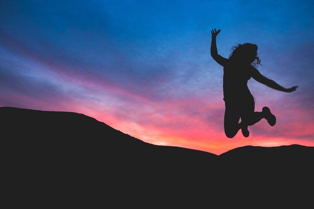 femme sautant face au soleil couchant