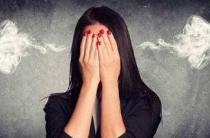 femme se couvrant le visage avec les mains