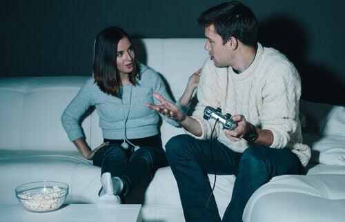 homme jouant aux jeux vidéos parlant avec sa compagne