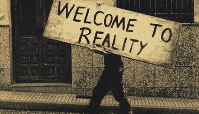 "personne portant un panneau ""welcome to reality"""