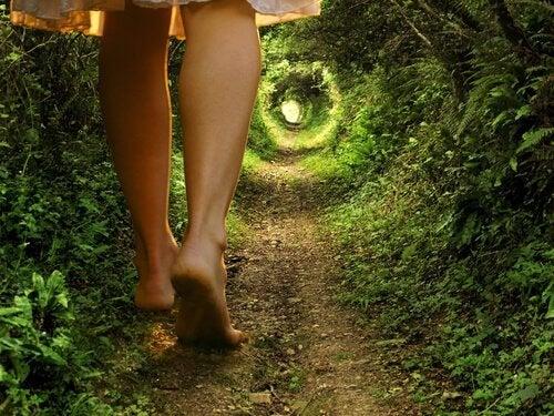 jambes d'une femme qui avance vers un jardin
