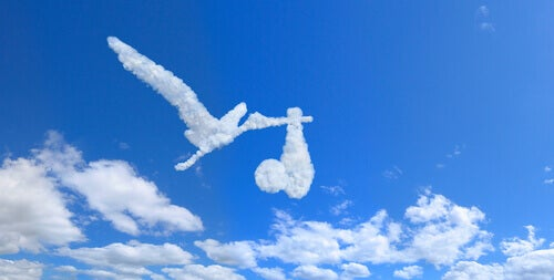 nuage en forme de cigogne portant un bébé
