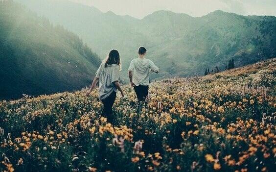 couple promenant dans un champ fleuri
