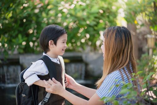 premier jour d'école pour un petit garçon parlant avec sa mère