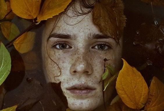 enfant entouré de feuilles