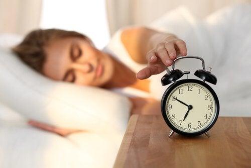 femme éteignant son réveil