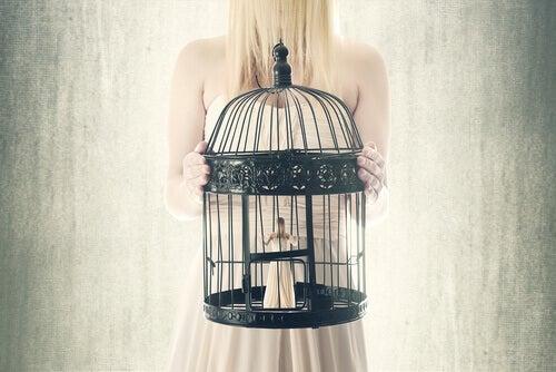 femme dans une cage du fait de son manque de défense appris