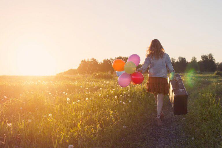 femme sur un chemin avec des ballons et une valise