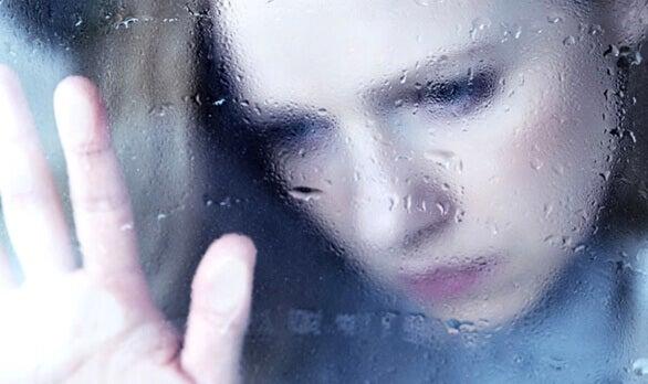 femme regardant par une fenêtre embuée