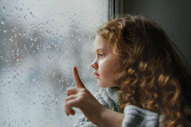 fille qui regarde par la fenetre pendant qu'il pleut