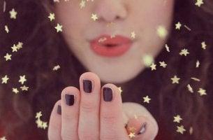 fille soufflant sur des paillettes en forme d'étoiles