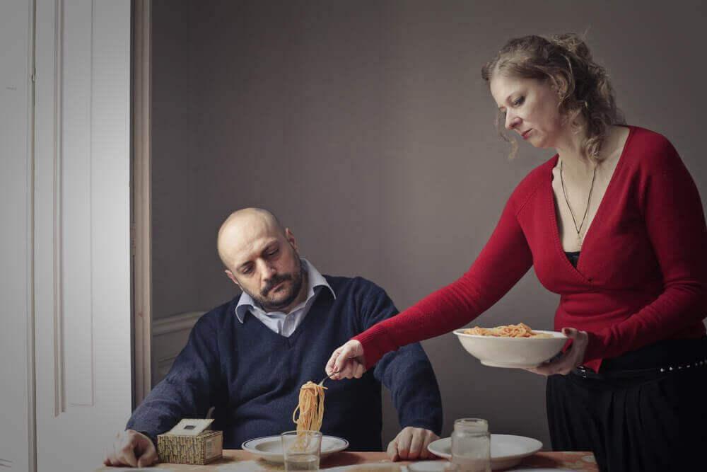 Femme servant de la nourriture à son mari